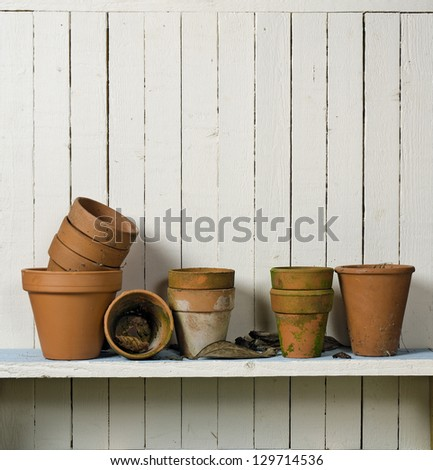 Vintage clay flowerpots on shelf; displayed in casual arrangements against rustic wall; good copy space - stock photo