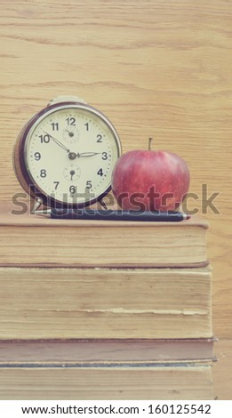 Vintage clock and apple with pancil on old books - stock photo