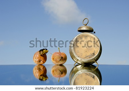 vintage clock and rotten apples on mirror - stock photo