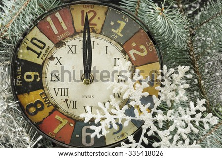 Vintage clock for New years eve, pointing at midnight and snowflakes