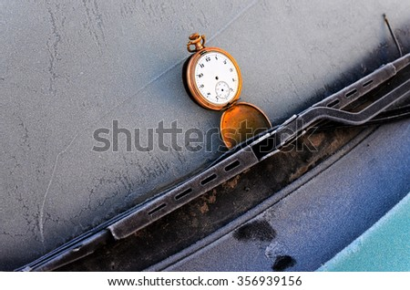 vintage clock on a frost car windshield - stock photo