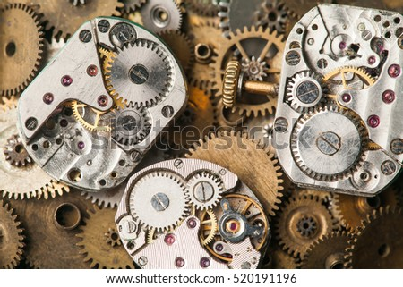 Vintage clocks mechanism close-up. Aged hand watches parts on bronze gears background