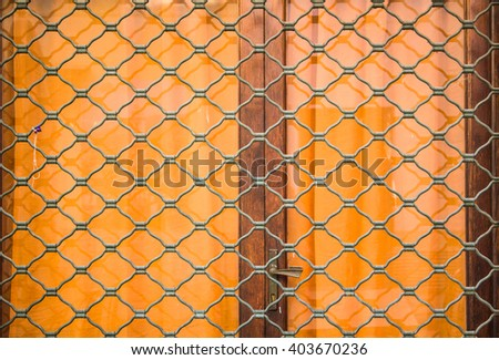 Vintage  Closed old wood door of an home, accents with an iron barred window, iron door knocker, and iron bolts. - stock photo