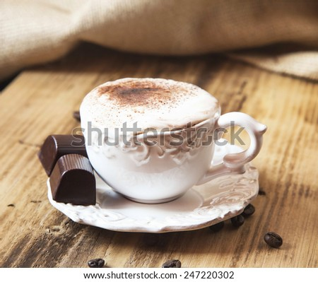 Vintage Coffee Cup with Cappuccino and Whipped Cream and Chocolate on Wooden Background - stock photo