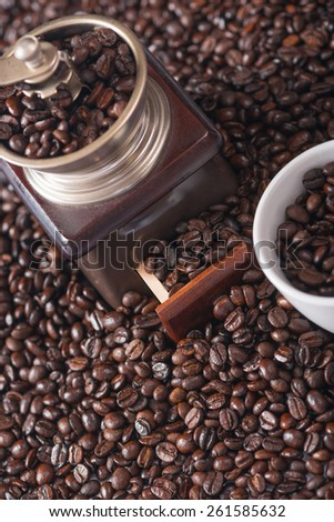 Vintage coffee grinder with coffee beans around it - Old objects - stock photo