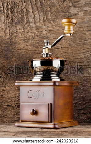 Vintage coffee grinder with coffee beans on wooden background