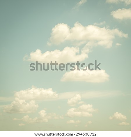 Vintage color style of blurred natural sky with soft clouds : Blur nature background of pale faded blue sky with puffy clouds in retro style effect: Holiday summer travel sky   - stock photo