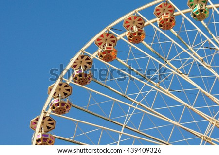 Vintage colorful ferris wheel against a sunny blue sky. Retro fun at a summer fair or a carnival. - stock photo