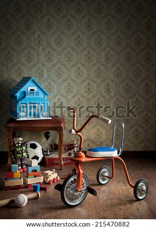 Vintage colorful tricycle with vintage toys and retro wallpaper on background. - stock photo