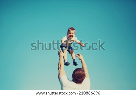 Vintage colors photo happy father and child having fun outdoors, carefree, blue sky, family, travel, vacation, childhood, father's day - concept