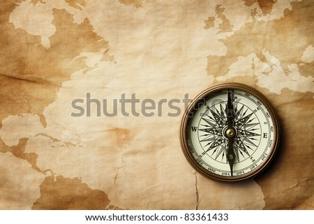 Vintage compass at old crumpled world map with copy space - stock photo