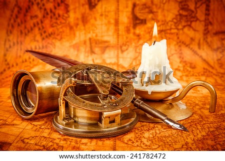 Vintage compass, magnifying glass, quill pen, spyglass lie on an old ancient map in 1565 with a lit candle. Vintage still life. - stock photo