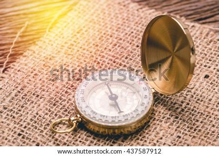 Vintage compass on sackcloth - stock photo