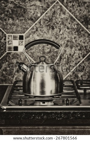 Vintage concept of a stainless steel tea pot on stove top.  - stock photo