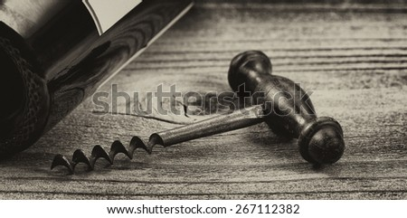 Vintage concept of antique corkscrew, focus on front lower part of corkscrew, with wine bottle in background on rustic wood. Horizontal layout.  - stock photo