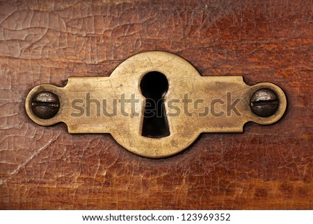 Vintage copper keyhole decorative element on weathered wooden surface - stock photo
