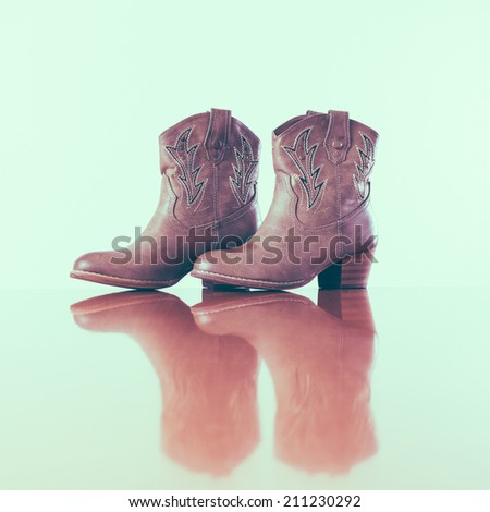 Vintage cowboy boots with reflection in wooden floor - stock photo