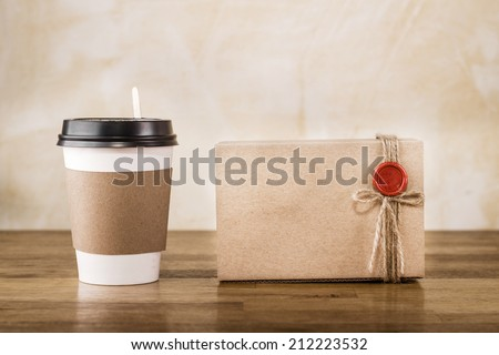 Vintage craft paper cup and package on wooden table - stock photo