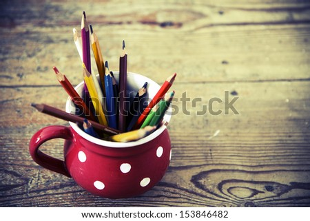 vintage crayons in the red cup on the wood floor - stock photo
