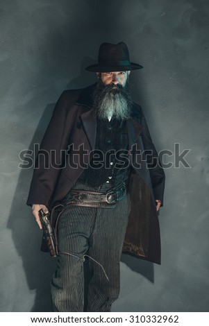 Vintage crook with long beard holding gun in 1900 style clothing against grey wall. - stock photo