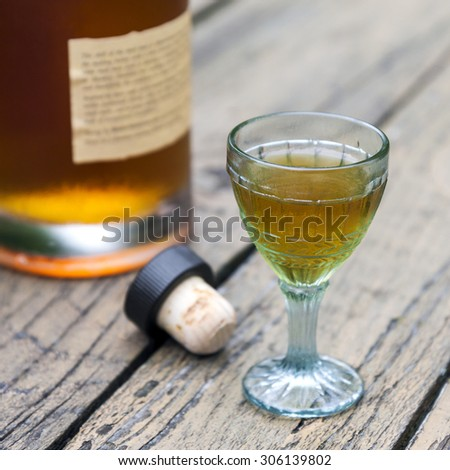 Vintage crystal brandy glass with bottle and cork in the background - stock photo