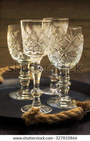 Vintage crystal glasses on the black tray with christmas decorations. Toned picture