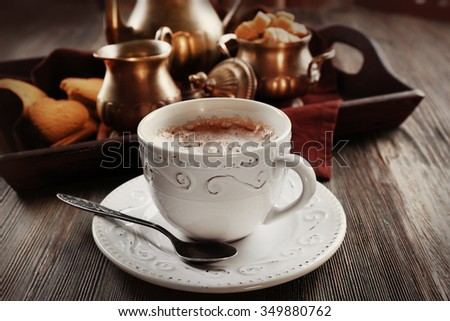 Vintage cup of cacao on wooden table against tray with silver service and cookies - stock photo