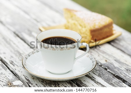 Vintage cup of coffee and saucer with a cake out of focus - stock photo