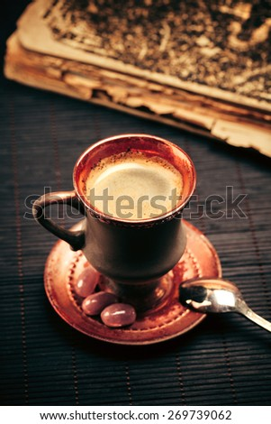 Vintage cup of coffee with foam, silver spoon and old book - stock photo