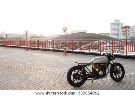 Vintage custom caferacer motorcycle in the parking lot during sunset. Outdoors lifestyle - stock photo