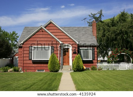 Vintage cute red house with white picket fence and red roses on arbor - stock photo