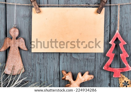 Vintage decorations in the shape of Christmas tree and  angel and blank card for message hanging on string on old wooden background - stock photo