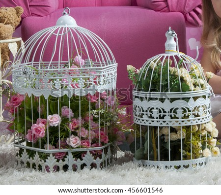 Vintage decorative bird cages full of flowers - stock photo