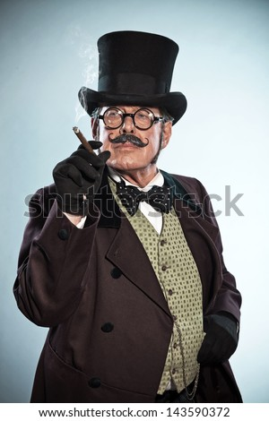 Vintage dickens style man with mustache and hat. Smoking cigar. Studio shot.