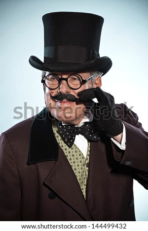 Vintage dickens style man with mustache and hat. Wearing glasses. Studio shot. - stock photo