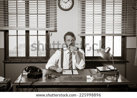 Vintage director working at office desk and looking at camera.