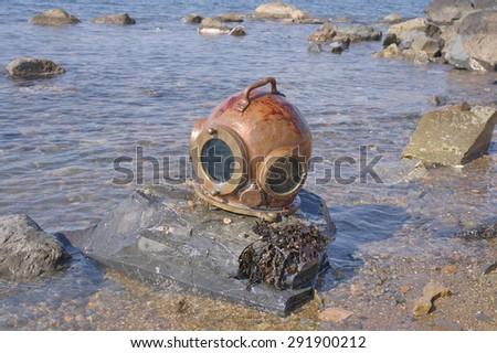 Vintage diving helmet on the rocky seashore. - stock photo