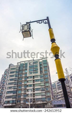 Vintage electrical streetlamp with high rise building background - stock photo