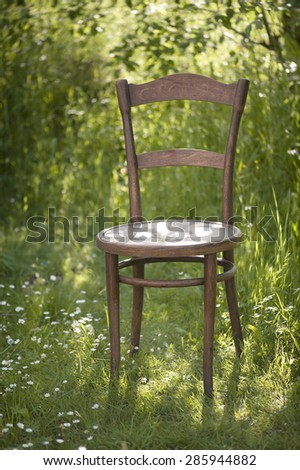Vintage Empty Chair In Fresh Green Sunny Garden - stock photo