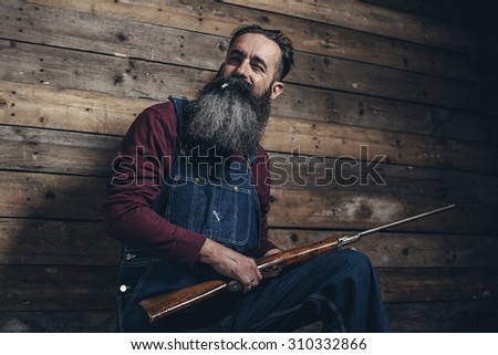 Vintage farmer holding rifle standing against wooden wall in barn. - stock photo
