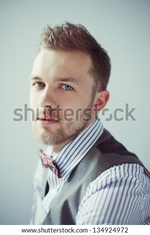 Vintage fashion portrait of young business man in bowtie with suit - stock photo