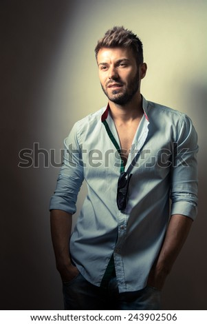 Vintage fashion portrait of young man in blue shirt posing over wall with contrast shadows - stock photo