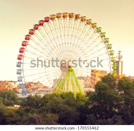 Vintage Ferris wheel looming above trees will - stock photo