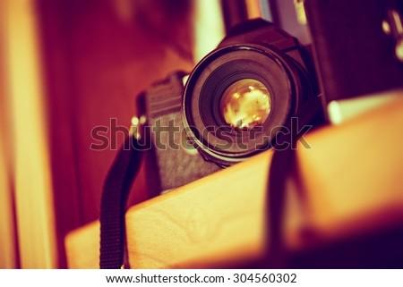 Vintage Film Camera on a Bookshelf. Aged Camera Closeup. Photography Technologies. - stock photo