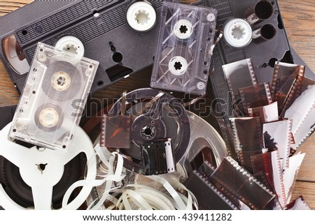 Vintage film camera rolls, old audio and video casettes with tape and foto strip on wooden background - stock photo