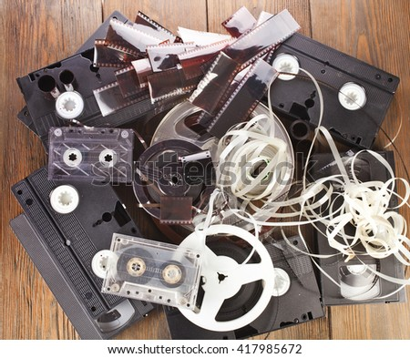 Vintage film camera rolls, old audio and video casettes with tape and foto strip on wooden table, top view - stock photo