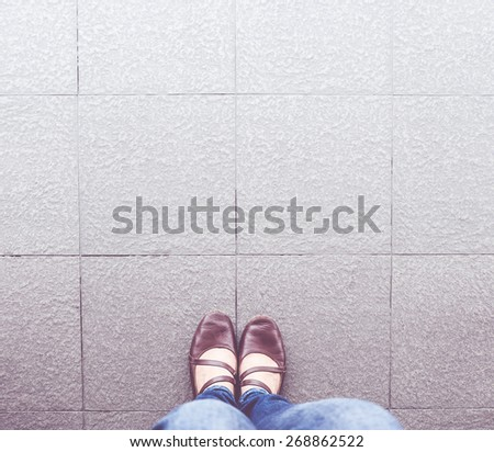 Vintage filter : aerial view of woman shoe wear blue jean stand on pavement. - stock photo