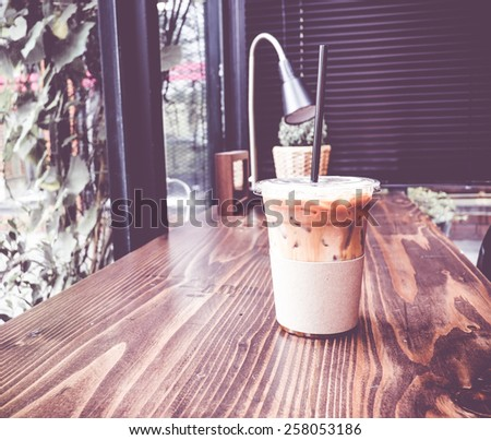 Vintage filter :Ice coffee on wood table beside window in coffee shop at garden - stock photo