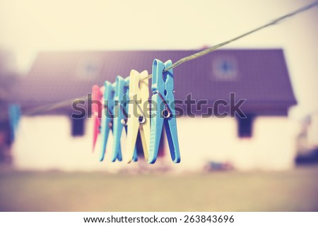Vintage filtered clothespins hanging on a cord in front of house, concept photo. - stock photo