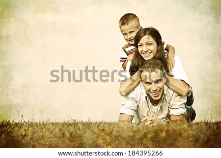 Vintage filtered image of a family lying on green summer grass meadow having happy life